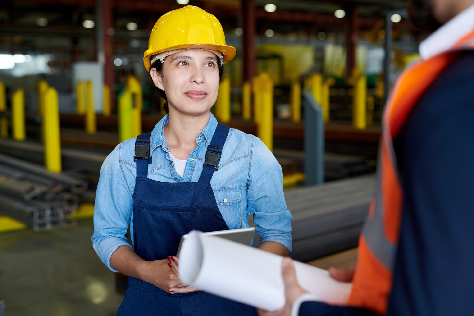 Female Factory Worker Listening to Foreman