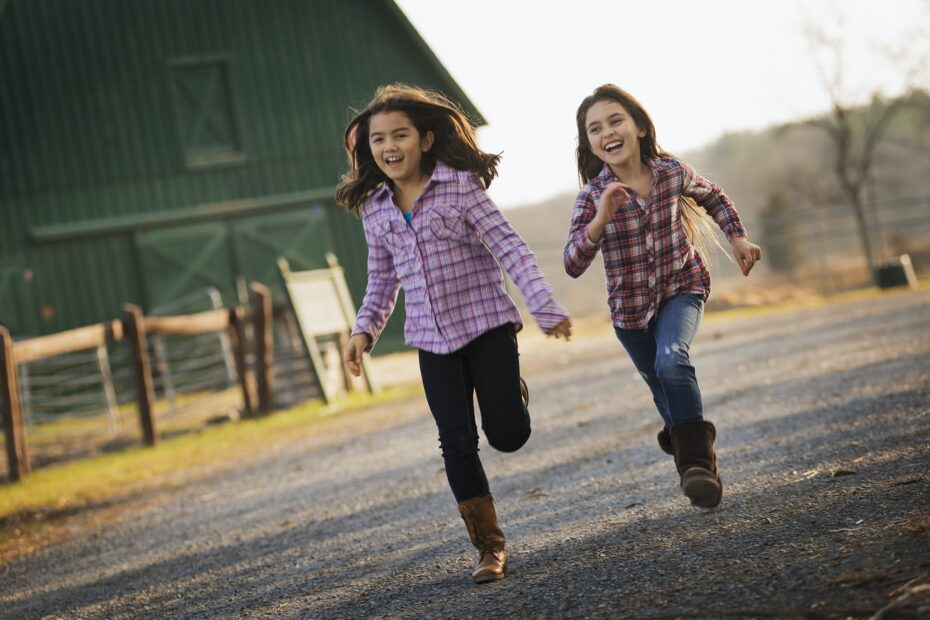 Two children running along a road, by a farm building, on an organic farm.
